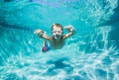 Muchacho joven que se zambulle bajo el agua en piscina Imágenes de archivo libres de regalías