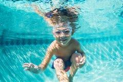 Muchacho joven que se zambulle bajo el agua en piscina Imagen de archivo libre de regalías