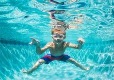 Muchacho joven que se zambulle bajo el agua en piscina Fotografía de archivo libre de regalías
