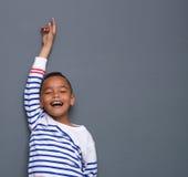 Muchacho joven que sonríe con el brazo aumentado Fotos de archivo