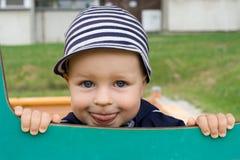 Muchacho joven que sonríe en el patio Foto de archivo