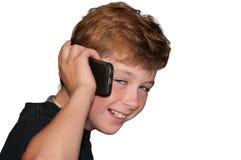 Muchacho joven que sonríe mientras que habla en un teléfono celular Fotos de archivo