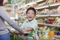 Muchacho joven que sonríe, sentándose en un carro de la compra, haciendo compras con la madre Fotografía de archivo libre de regalías