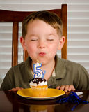 Muchacho joven que sopla hacia fuera la vela del cumpleaños Foto de archivo libre de regalías