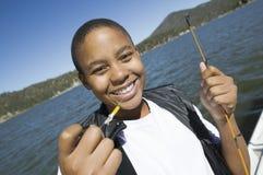 Muchacho joven que sostiene cebo de pesca imagen de archivo libre de regalías