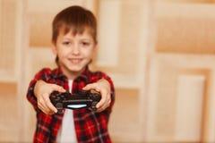 Muchacho joven que sostiene el regulador del juego que juega a los videojuegos Foto de archivo libre de regalías