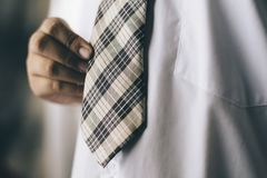 Muchacho joven que sostiene el suyo lazo/corbata Imagenes de archivo