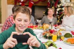 Muchacho joven que sostiene smartphone durante cena de la Navidad Fotos de archivo