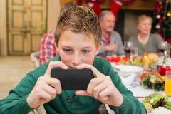 Muchacho joven que sostiene smartphone durante cena de la Navidad Imagenes de archivo