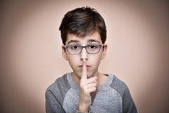 Muchacho joven que sostiene un dedo índice en sus labios Fotos de archivo libres de regalías