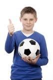 Muchacho joven que sostiene una bola del fútbol Foto de archivo