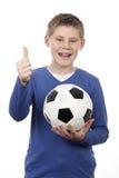 Muchacho joven que sostiene una bola del fútbol Imágenes de archivo libres de regalías