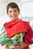 Muchacho joven que sostiene una pila de lavadero Fotos de archivo