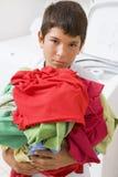 Muchacho joven que sostiene una pila de lavadero Fotos de archivo libres de regalías