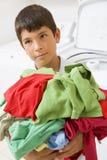 Muchacho joven que sostiene una pila de lavadero Imagen de archivo libre de regalías