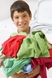 Muchacho joven que sostiene una pila de lavadero Foto de archivo