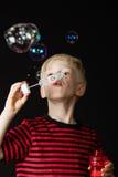 Muchacho joven que tiene burbujas de jabón de la diversión que soplan Imagenes de archivo