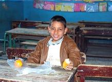 Muchacho joven que tiene su comida en la escuela en clase Foto de archivo