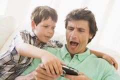 Muchacho joven que toma el juego handheld del hombre Fotos de archivo