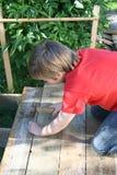 Muchacho joven que trabaja con el martillo Foto de archivo