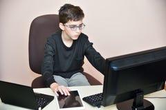 Muchacho joven que trabaja en los ordenadores Foto de archivo