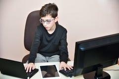 Muchacho joven que trabaja en los ordenadores Fotografía de archivo libre de regalías
