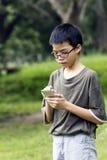Muchacho joven que usa el teléfono móvil Fotografía de archivo libre de regalías