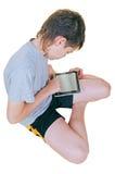 Muchacho joven que usa la tablilla electrónica en el país Fotografía de archivo