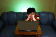 Muchacho joven que usa un ordenador portátil y una sonrisa Imagenes de archivo
