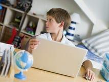 Muchacho joven que usa una computadora portátil en su dormitorio imagenes de archivo