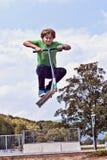 Muchacho joven que va aerotransportado con su vespa imagen de archivo libre de regalías