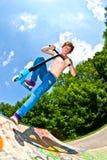 Muchacho joven que va aerotransportado con una vespa Fotografía de archivo
