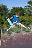 Muchacho joven que va aerotransportado con una vespa Fotografía de archivo libre de regalías