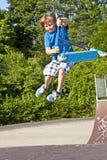 Muchacho joven que va aerotransportado con una vespa Foto de archivo libre de regalías
