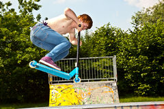 Muchacho joven que va aerotransportado con una vespa Fotos de archivo libres de regalías