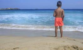 Muchacho joven que ve el mar imagen de archivo