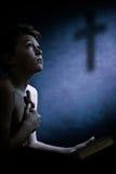 Muchacho joven religioso que abrocha una cruz Imágenes de archivo libres de regalías