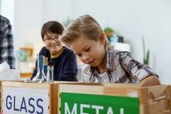 Muchacho joven resuelto exacto que saca el elemento plástico de la botella de cristal imágenes de archivo libres de regalías