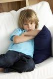 Muchacho joven Sat en el sofá en el país foto de archivo libre de regalías