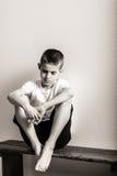 Muchacho joven solo que se sienta en banco con las rodillas para arriba imagen de archivo