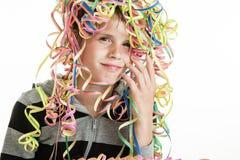 Muchacho joven sonriente con las flámulas del partido en su cabeza Imagenes de archivo