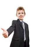 Muchacho joven sonriente del niño del hombre de negocios que gesticula el pulgar encima de la muestra del éxito Imagenes de archivo