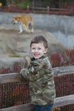 Muchacho joven sonriente en el parque zoológico Imagenes de archivo