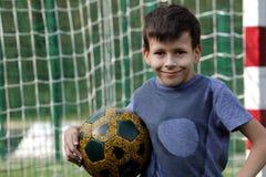 Muchacho joven sonriente feliz con la bola del fútbol Imagenes de archivo