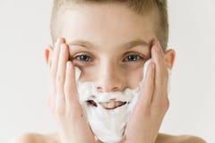 Muchacho joven sonriente que aplica la crema de afeitar a la cara Fotografía de archivo libre de regalías