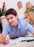 Muchacho joven sonriente que miente con el libro en sala de estar Fotografía de archivo