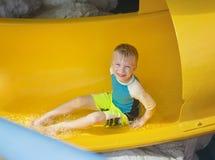 Muchacho joven sonriente que monta abajo de un tobogán acuático amarillo Fotografía de archivo libre de regalías