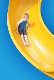 Muchacho joven sonriente que monta abajo de un tobogán acuático amarillo Fotografía de archivo