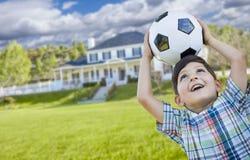 Muchacho joven sonriente que sostiene el balón de fútbol delante de la casa Foto de archivo libre de regalías