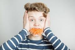 Muchacho joven torpe con un bocado de la zanahoria Fotos de archivo